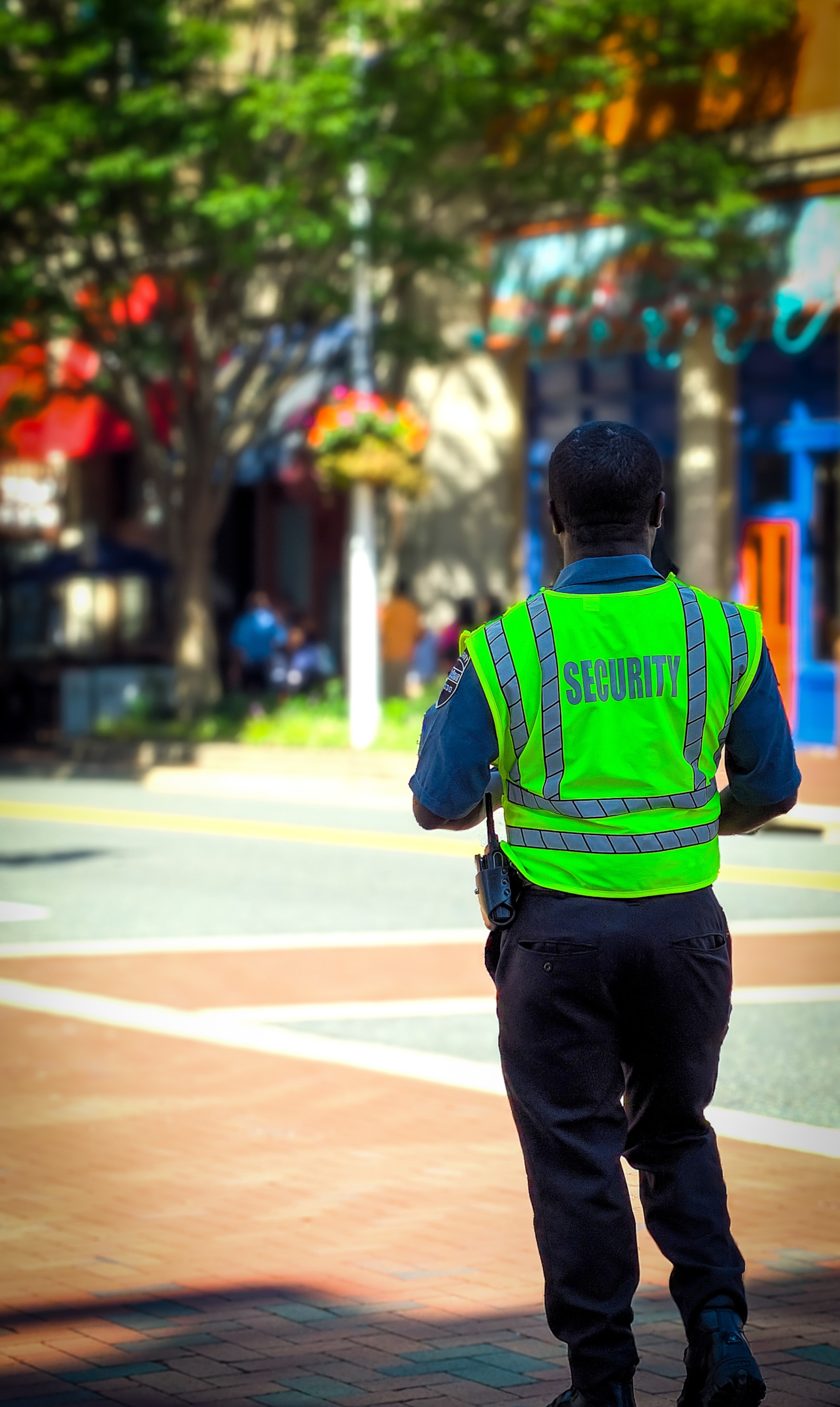 (Source: unsplash.com/@thenewmalcolm) Security Guard in a neon green vest watches over a 4way intersection