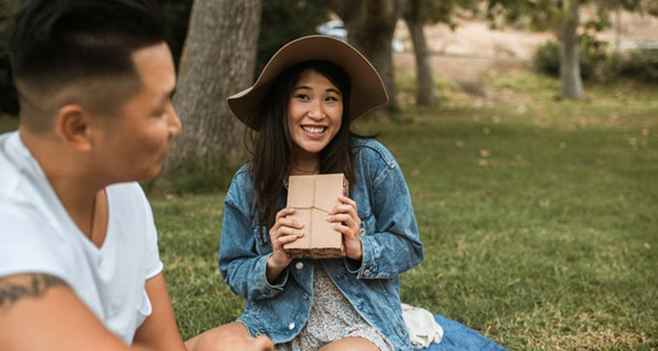 A girl offering a guy she likes a gift package while on a picnic https://www.bonobology.com/girl-likes-hiding/