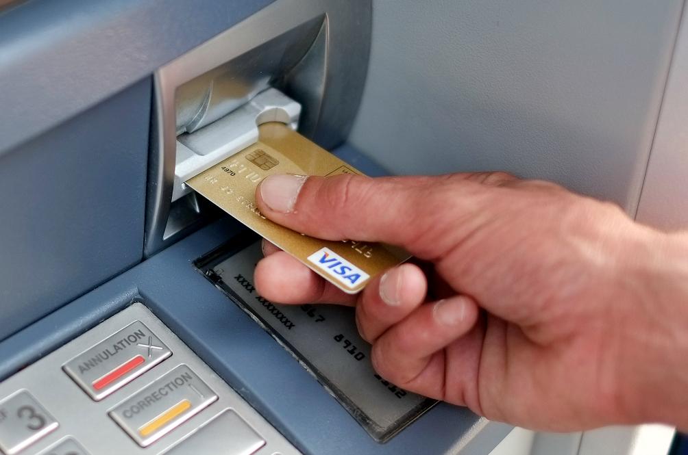 inserting debit card into atm