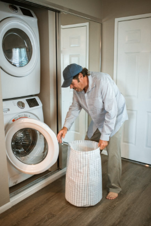 man doing laundry in house