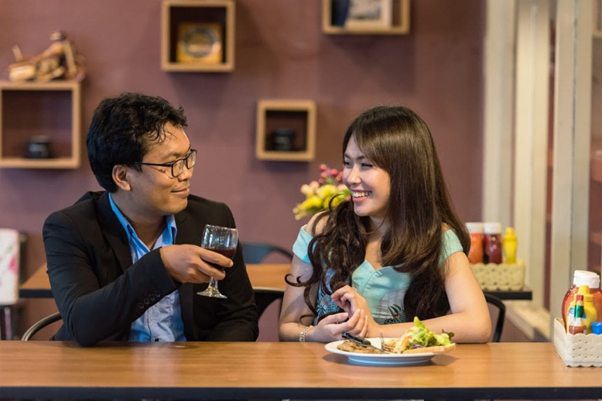 A girl and a guy conversing over intimate home dinner https://hackspirit.com/how-to-get-girl-like-you/