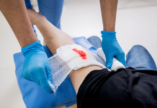 An image of a healthcare provider placing a bandage on a small wound.