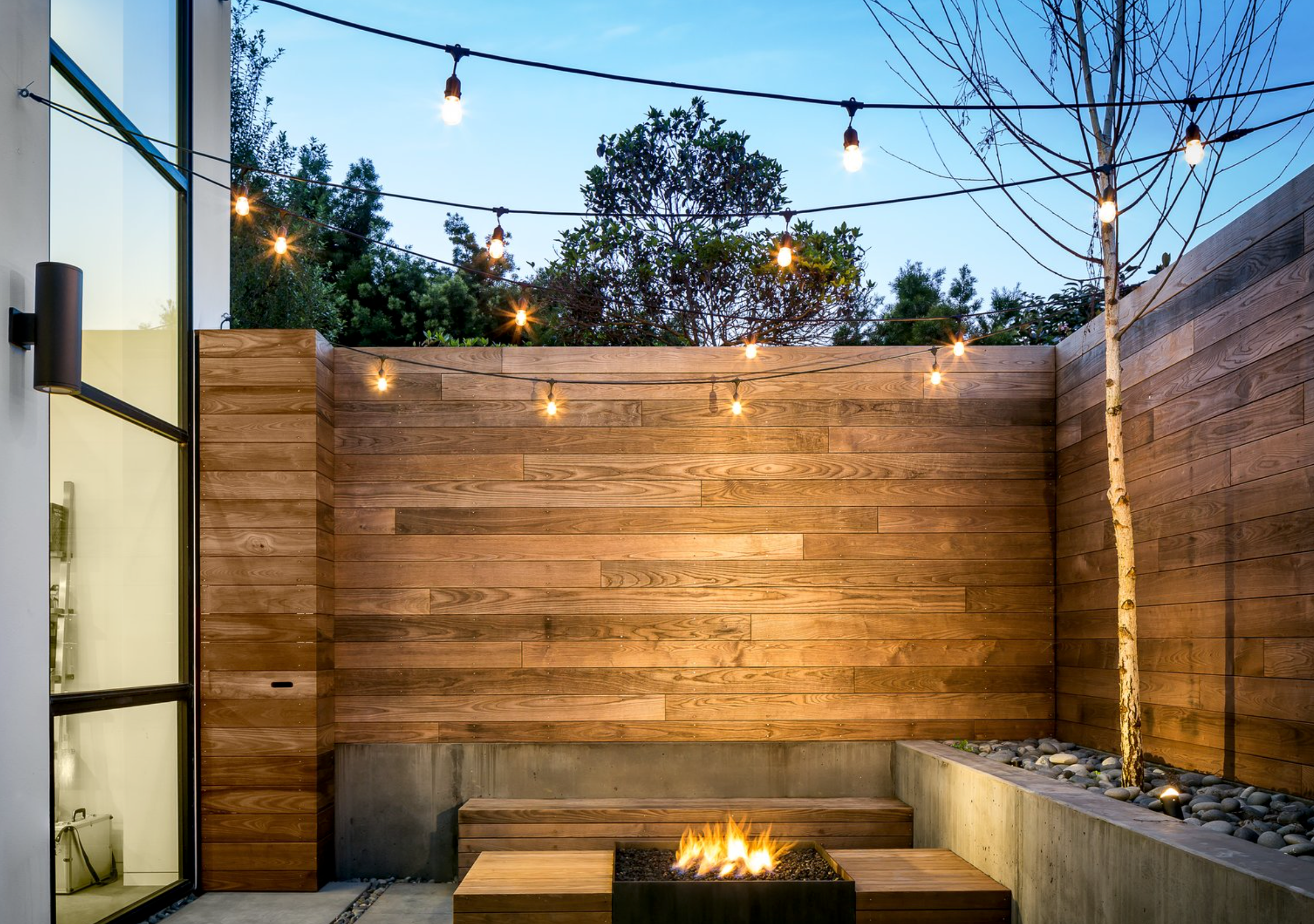 Wall lights on wooden fence with overhead bulbs