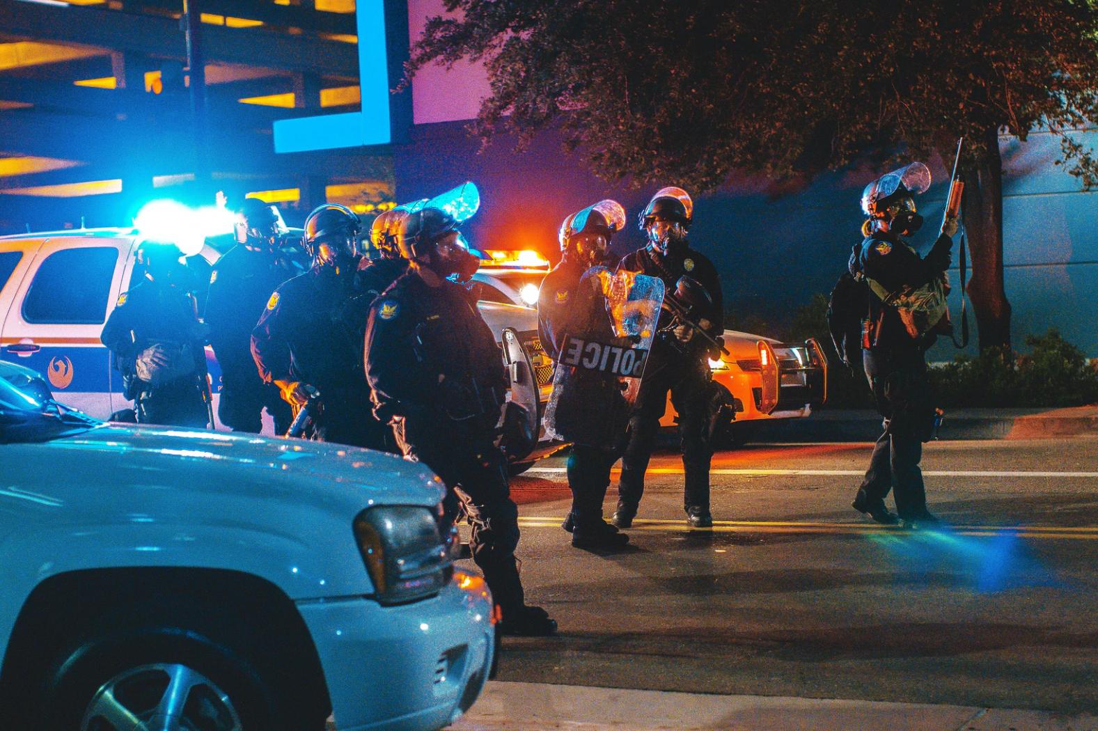 (Source: unsplash.com/@ajcolores) Police wearing body armor prepare to confront protesters