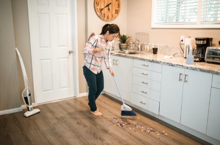 woman using broom to sweep