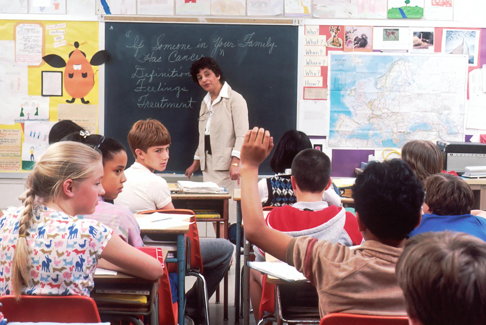 (Source: unsplash.com/@nci) School children having class with one raising his hand.