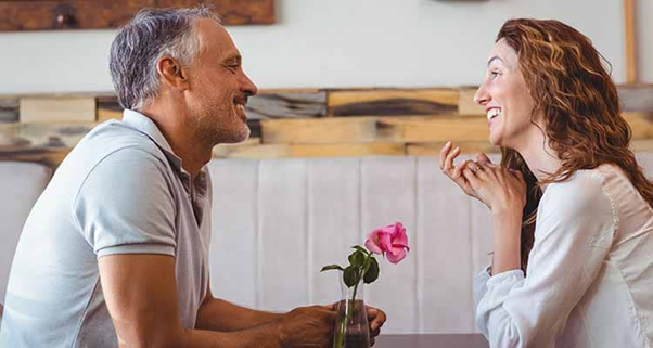 A man and a woman smiling at each other in a restaurant https://www.bonobology.com/signs-guy-loves-secretly/