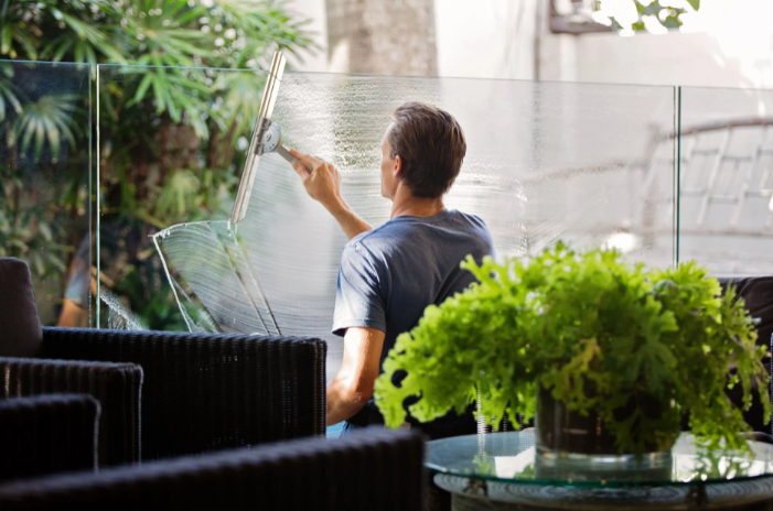 man cleaning clear glass wall