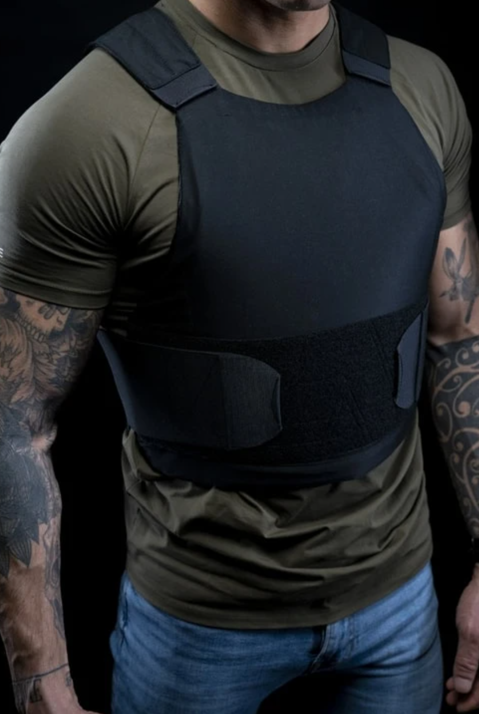 Tattooed man wearing PROTECTION GROUP DENMARK LEVEL IIIA ALPHA BULLET AND STAB PROOF VEST in black
